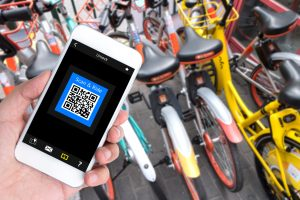 Bicycle sharing service or rental technology concept. Sharing economy and collaborative consumption. Customer hand using mobile phone to qr code application for ride bicycle.
